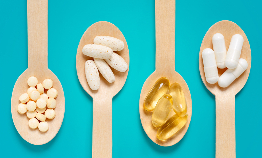 Pills and supplements on wooden spoons