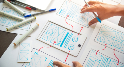 Person at desk with markers and a schematic for UX design