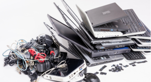 Older electronic devices, mouse, laptop computers, and cords piled together