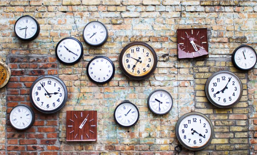 Wall of hanging analog clocks on a wall