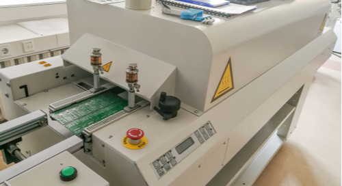 Picture of a circuit board solder reflow machine in PCB manufacturing