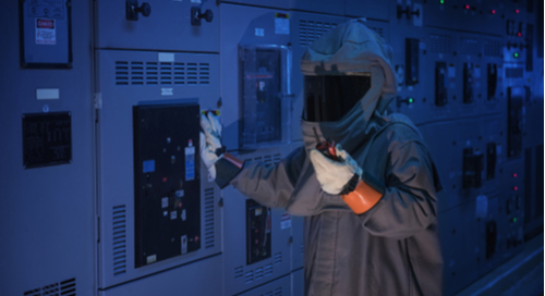 Engineer wearing arc flash prevention suit while testing electronics