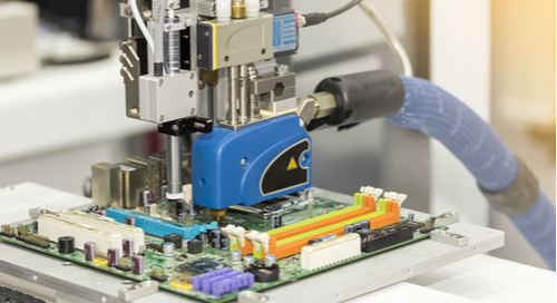 Fasteners being applied during the assembly of a printed circuit board