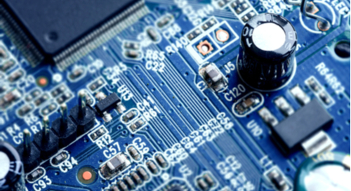 Blue PCB close-up with resistors, microcontrollers, and other SMT components