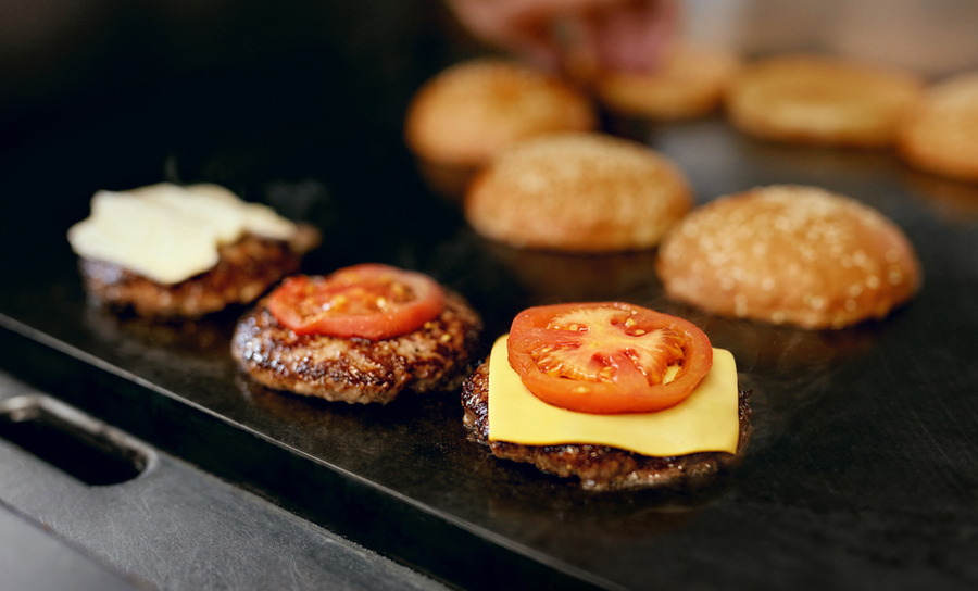 Picture of burgers on a restaurant grill in a cost value analysis