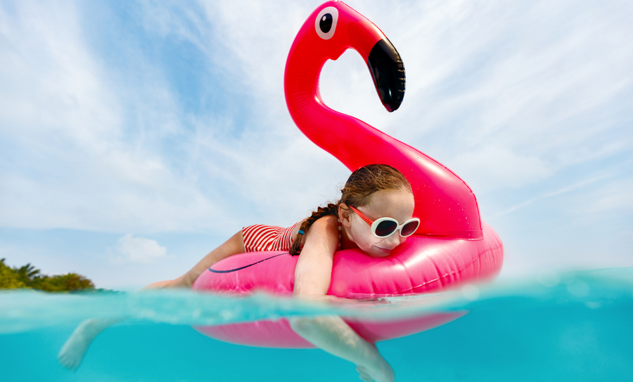 PIcture of young girl floating on an inflatable flamingo toy to cool off from the heat