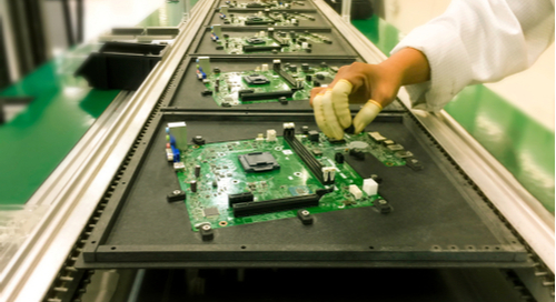 Picture of PCBs going through manual component insertion prior to wave soldering