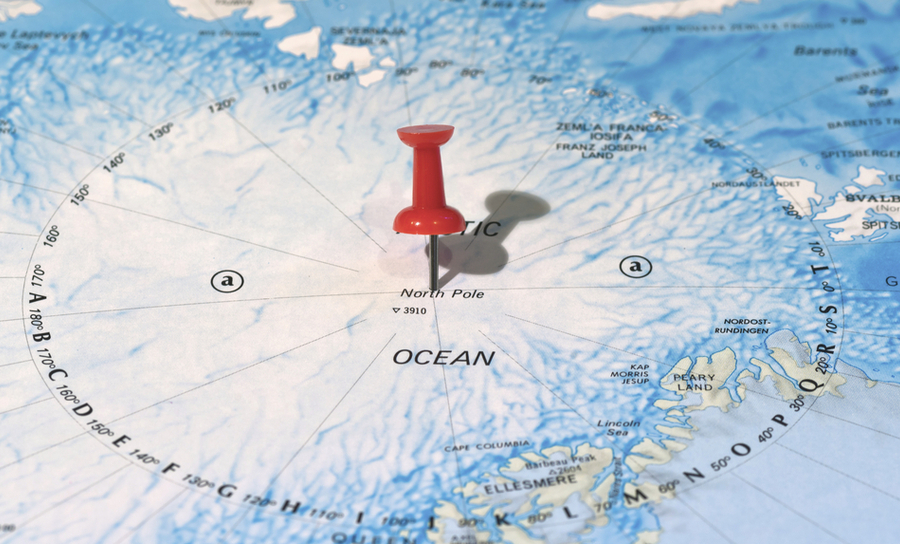 PIcture of the north pole with a thumbtack at its center on a map