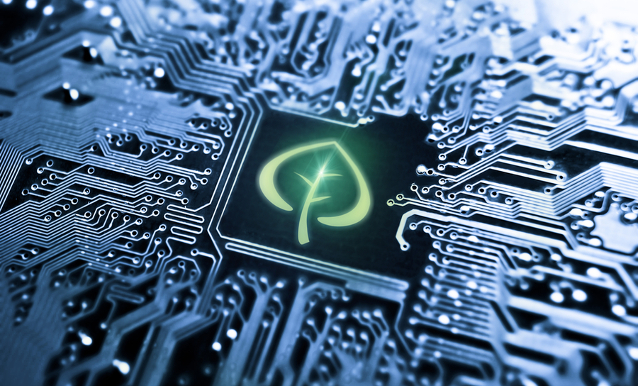 Circuit board with a graphic green leaf on it representing environmental awareness