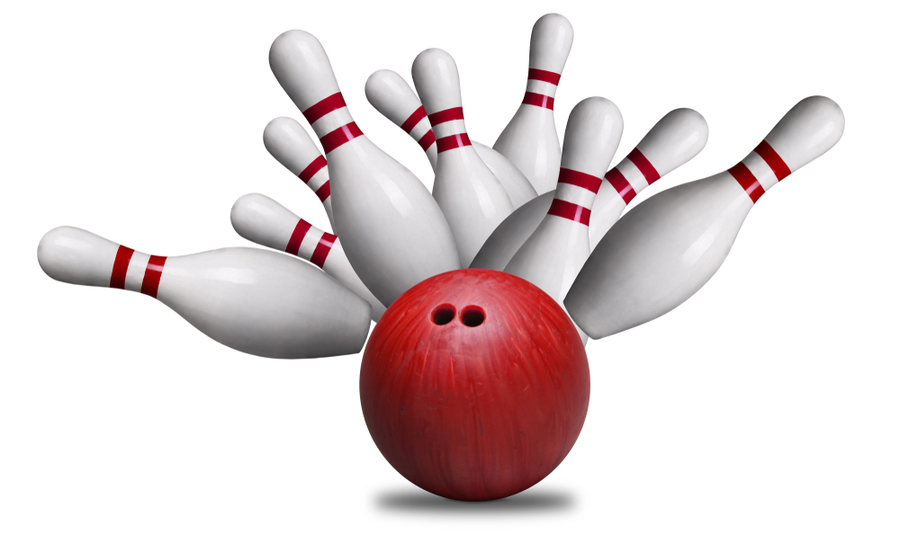 Bowling ball about to strike and knock over pins