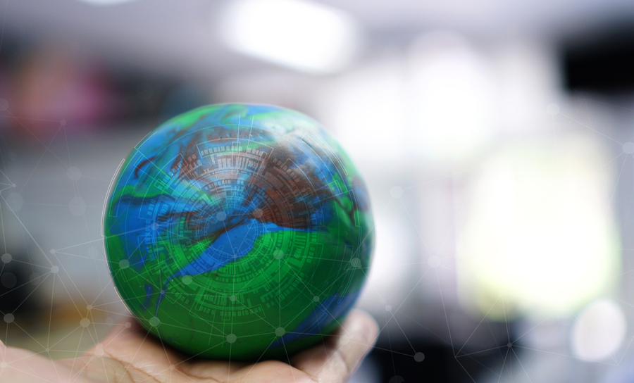 Globe being held in a hand with light background of routing