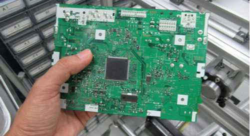 A person's hand holding a green printed circuit board (PCB)