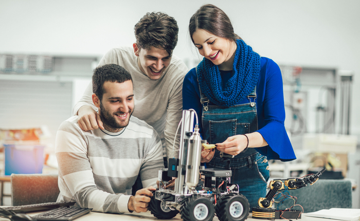 Two men and a woman happily look at their completed mechanical engineering project