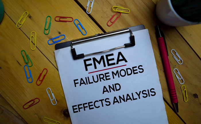 Failure mode and effects analysis (FMEA) written on paper isolated on a wooden background