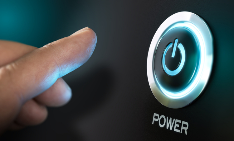 Human finger reaching for round button labeled as power