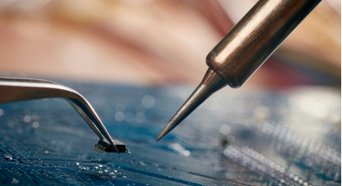Tweezers holding a microchip and a soldering iron