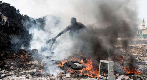A man setting fire to piles of e-waste