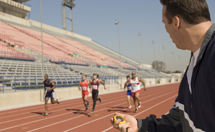 A man with a stopwatch overseeing multiple males athletes running on an outdoor track