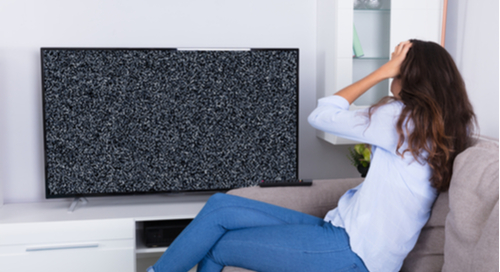 Woman visibly frustrated at a tv getting poor signal