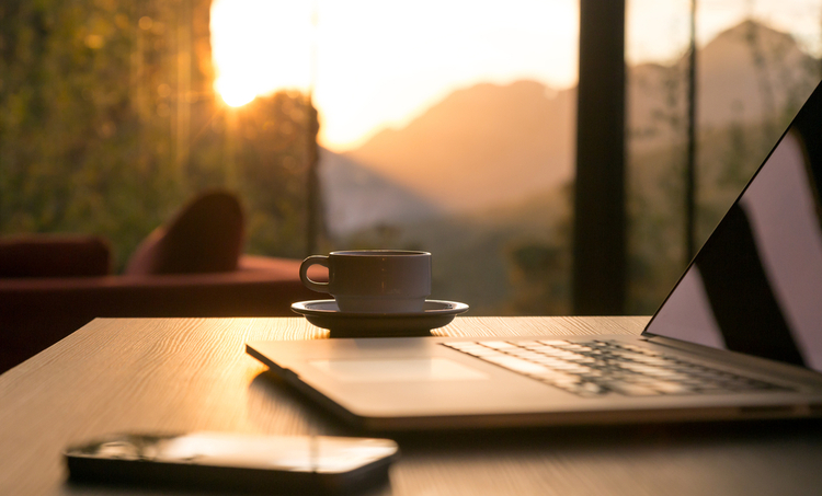 Coffee, computer and cell phone on a table in front of a window during sunrise