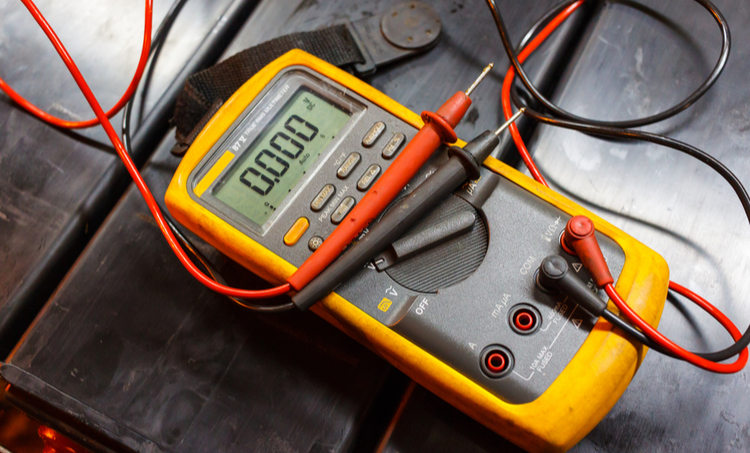 Digital multimeter with red and black probes on a black surface
