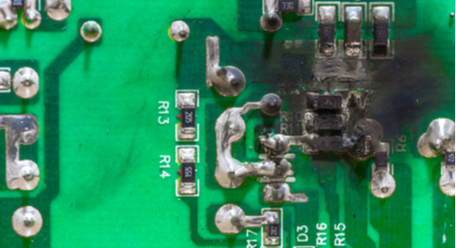 A circuit board with a burn mark from a short circuit