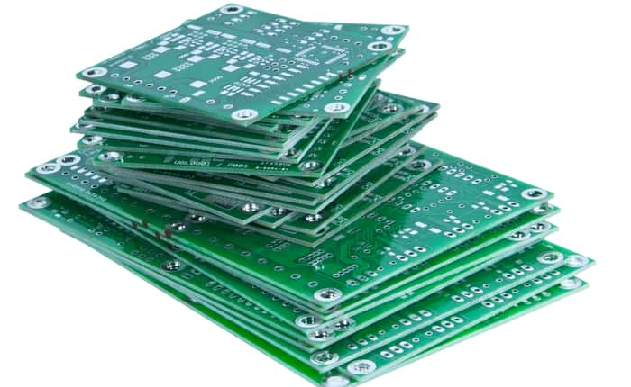 a stack of green, bare board PCBs