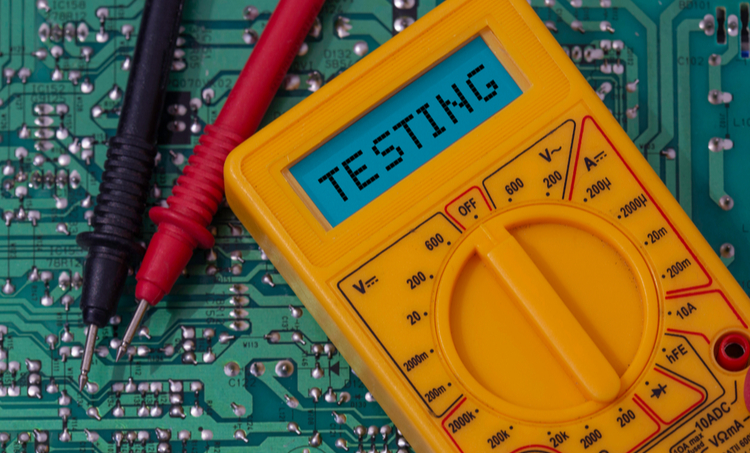 A yellow digital multimeter on a circuit board