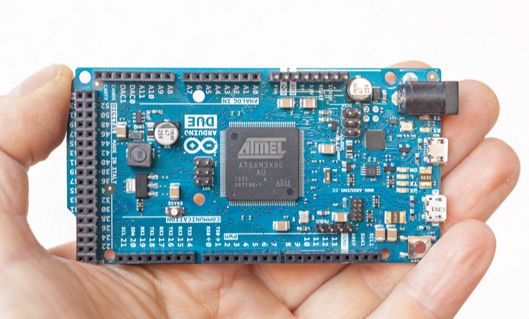 Human hand holding a printed circuit board with 32-bit microcontroller