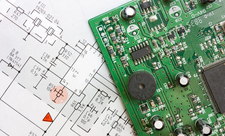 A PCBA on top of the electronic design software schematic it was created from