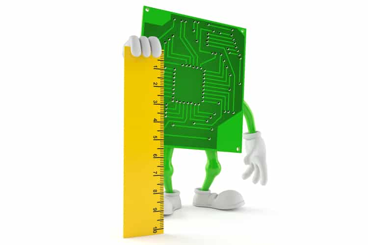 Image of a green circuit board with a ruler to measure trace widths and clearances