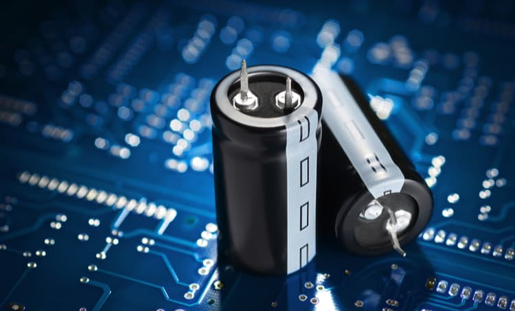 Two cylindrical capacitors sitting on top of a blue PCBA