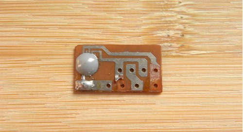 An epoxy resin coating on a small, brown PCB