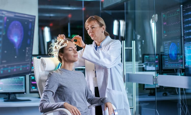 Researcher attaching brain scan equipment to a human subject