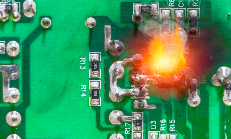 An overheated electronic component glowing orange on a PCB