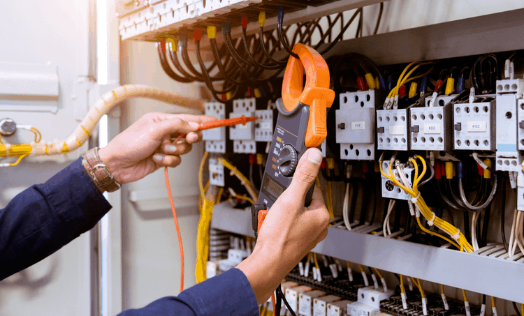 Man testing electric current in a control panel