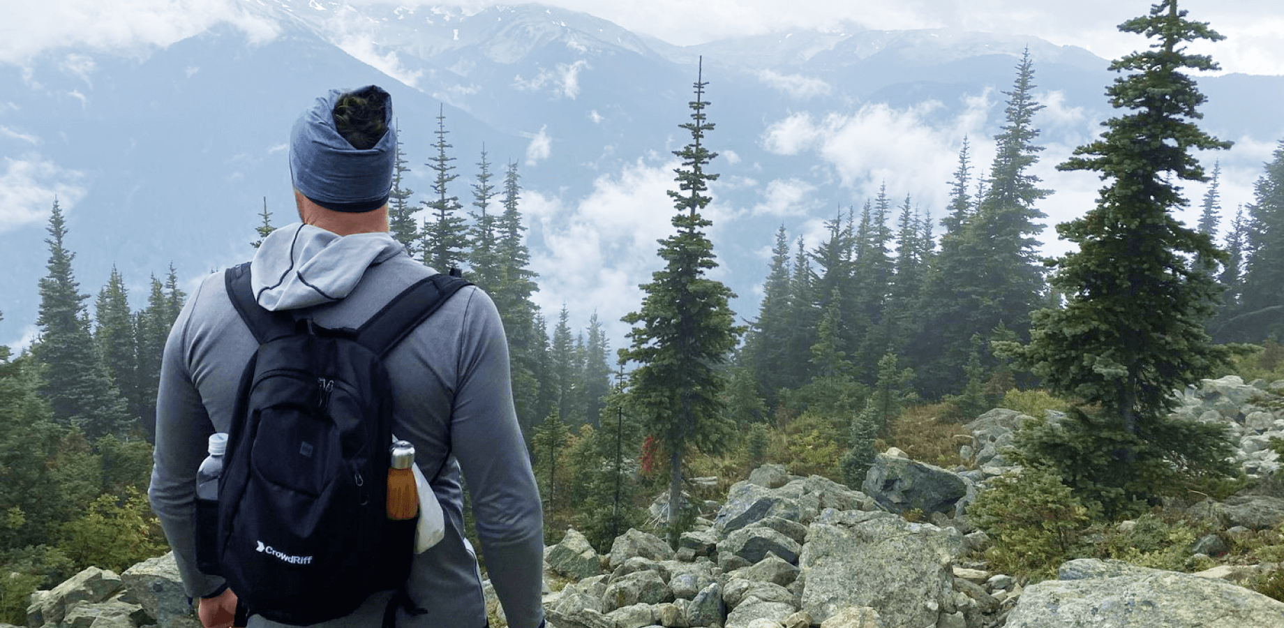 CrowdRiff employee looking over a mountainous landscape among trees
