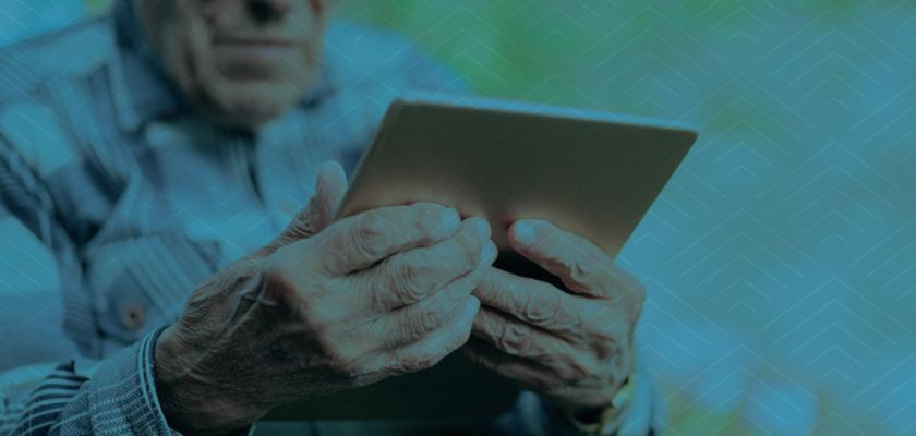Elderly man holding a tablet