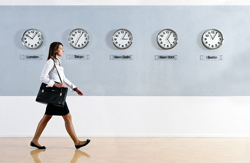 business woman walking in front of clocks