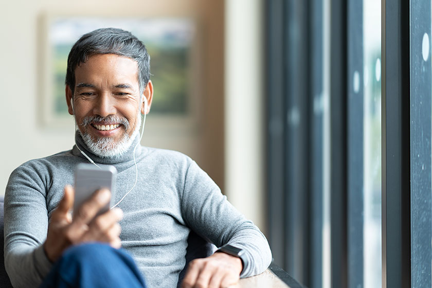 man listening to a podcast for finance leaders on his smartphone