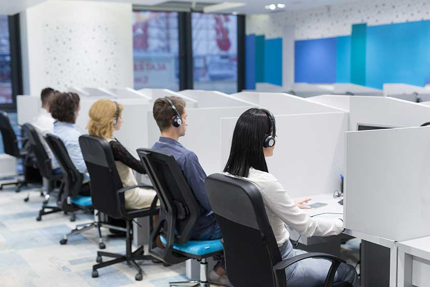 outsourced bookkeepers sitting in cubicles next to each other