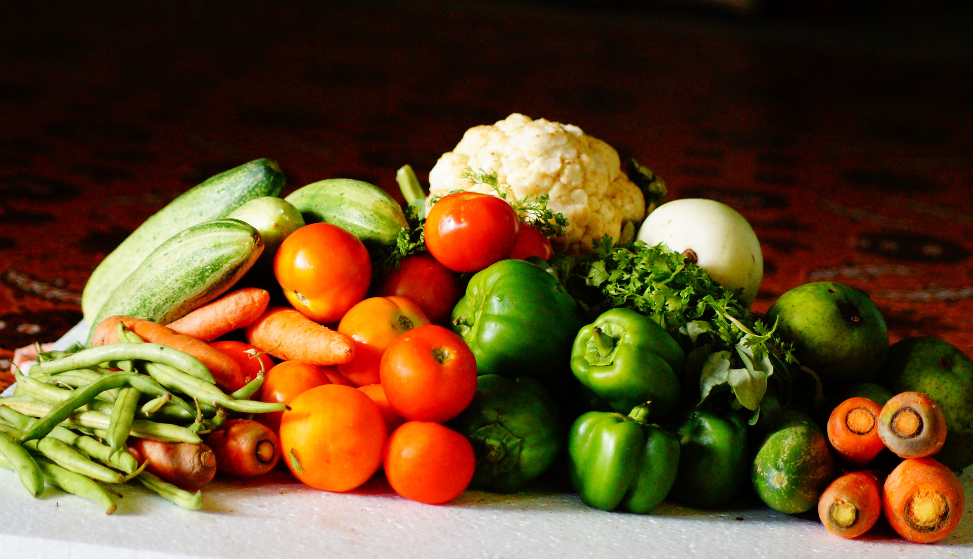 An array of different vegetables; tomatoes, peppers, cauliflower, carrots and string beans on a table. - TAB Bank