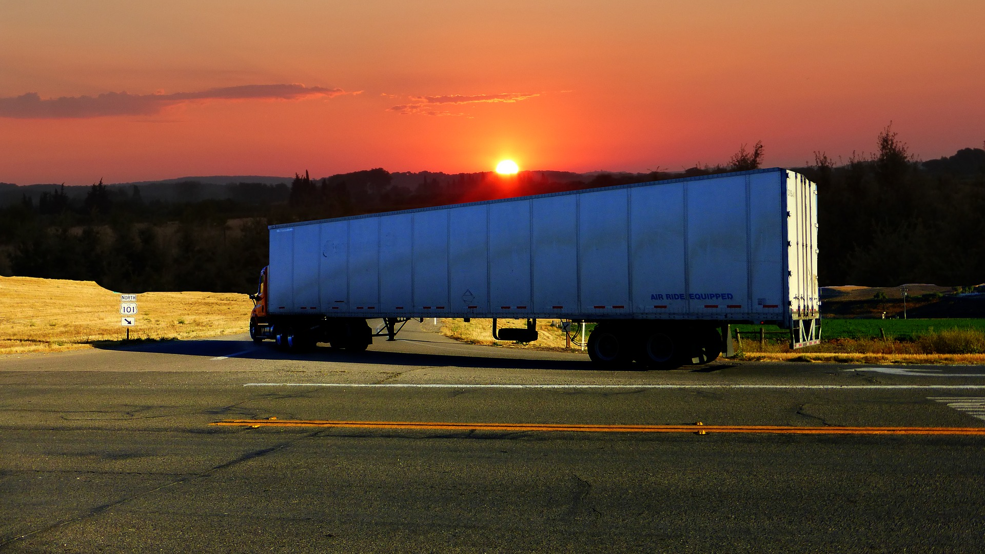 A white semi truck driving off a main road to a side road, towards the mountains and sunset. - TAB Bank
