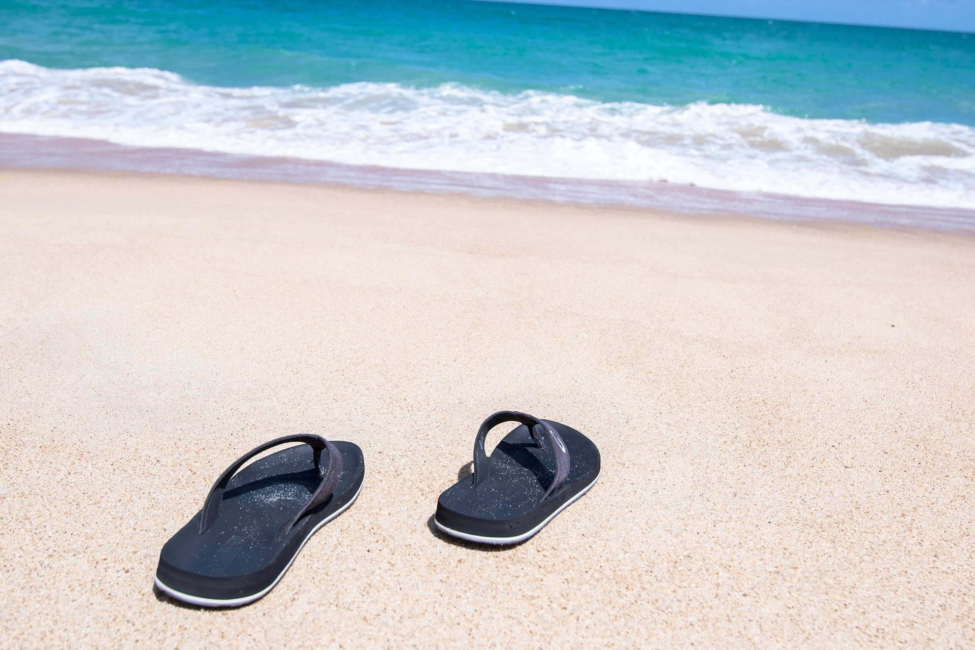 A pair of flip flops on a beach facing towards a body of water. - TAB Bank