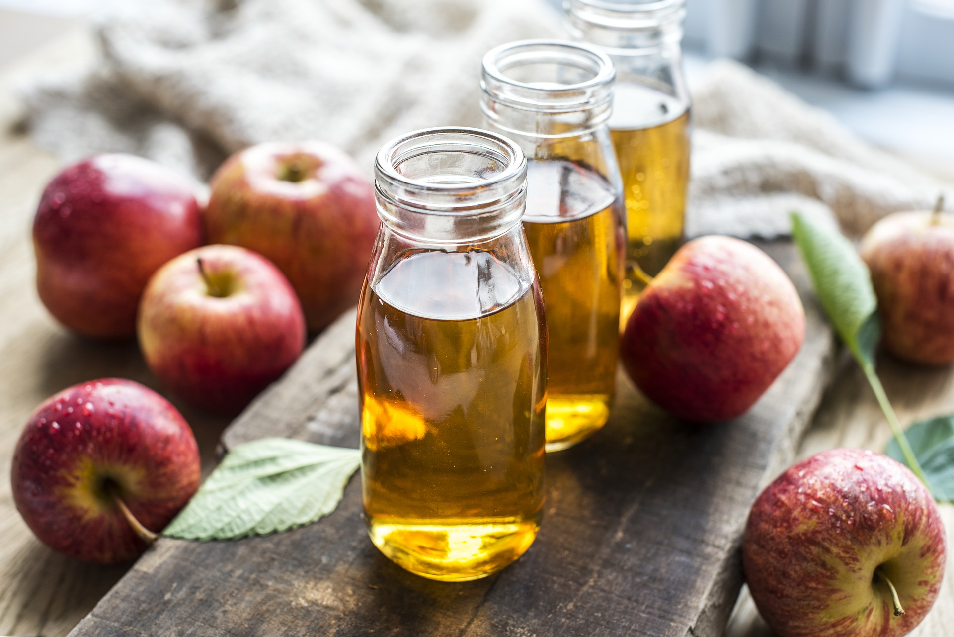 Three bottles of apple juice sitting on a plank of wood surrounded by apples and leaves. - TAB Bank