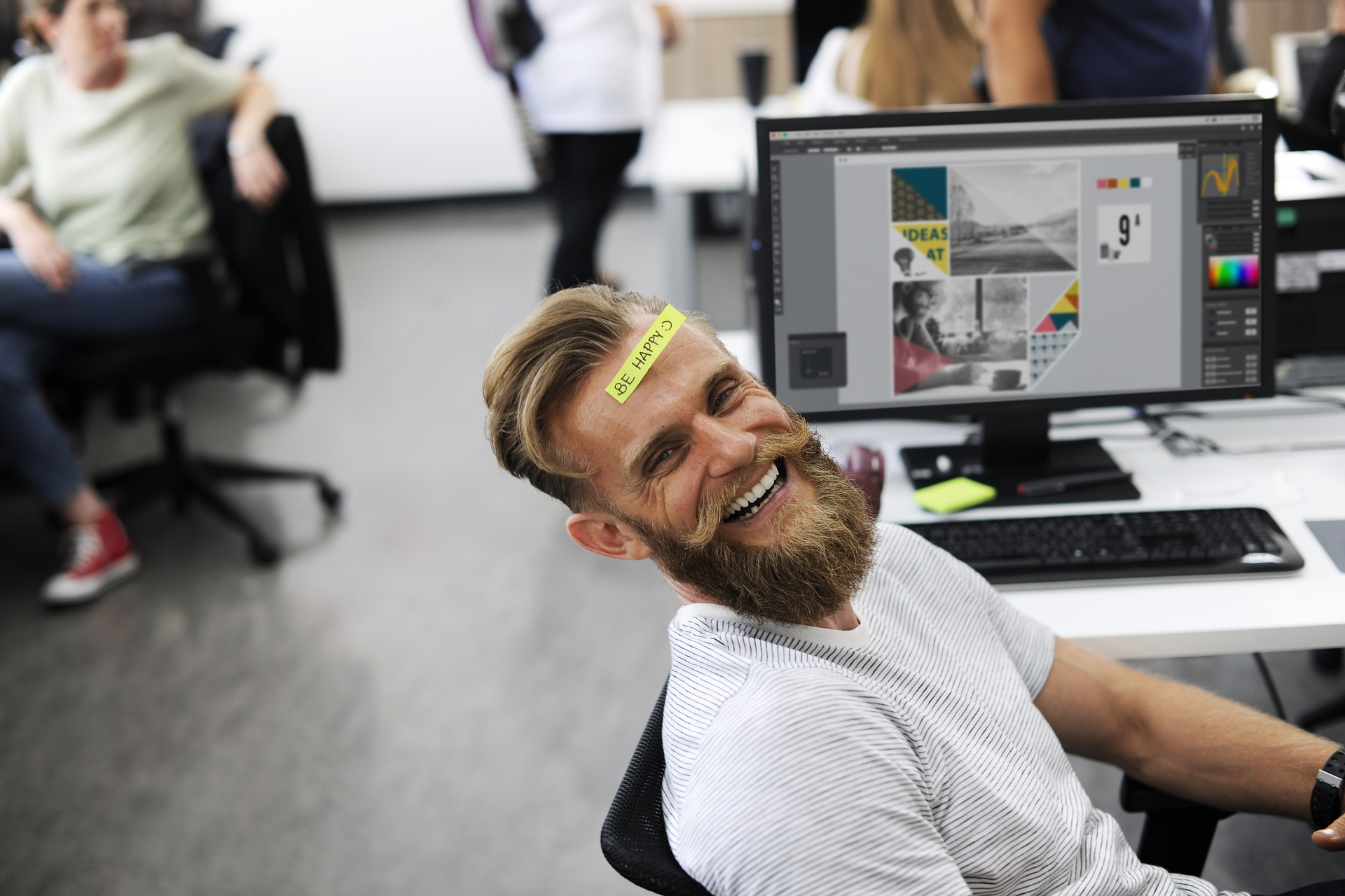 A man sitting in an open office setting  in front of his computer laughing with a note stuck to his head. Starting a business in Utah for the absolute beginner, man in office smiling