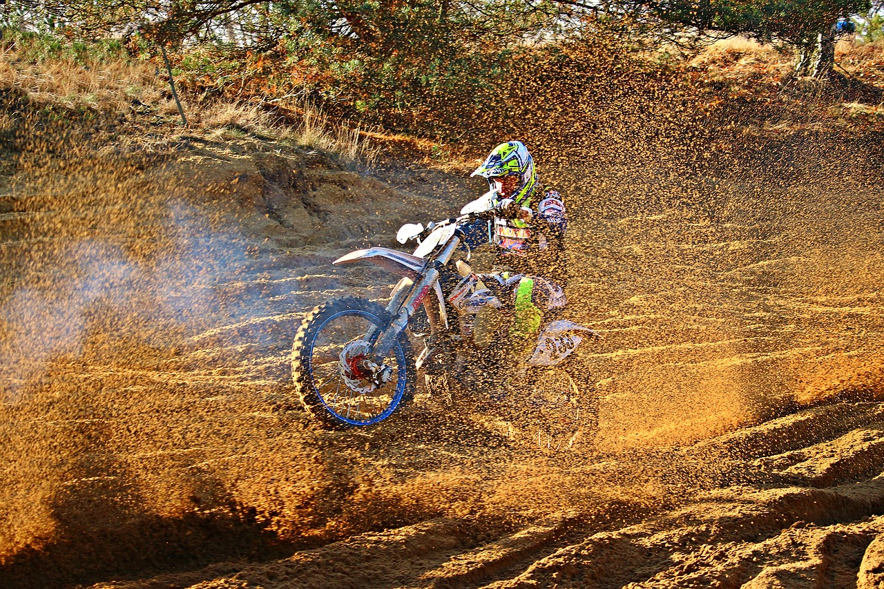 Motocross dirt bike rider on a track with dirt and mud flying all over. TAB Bank funds motocross apparel company with a $600,000 revolving credit facility. - TAB Bank
