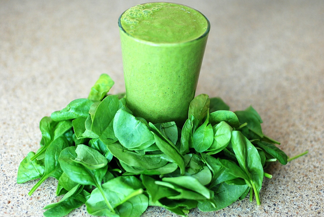 Image of spinach on a table with a spinach smoothie in a glass in the center - TAB Bank