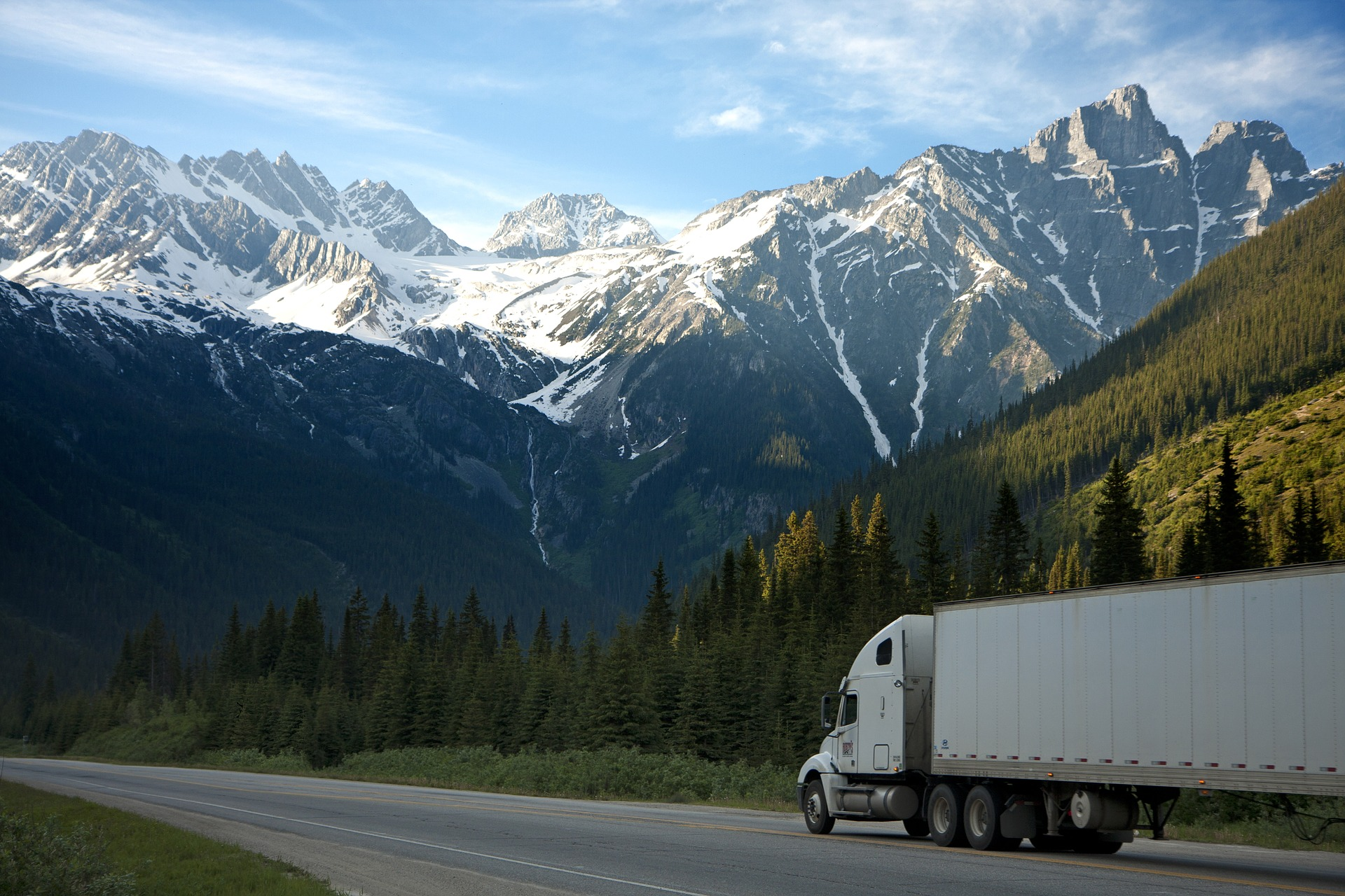 Image of a semi-truck on a highway beneathe a backdrop of snow covered mountain peaks - TAB Bank