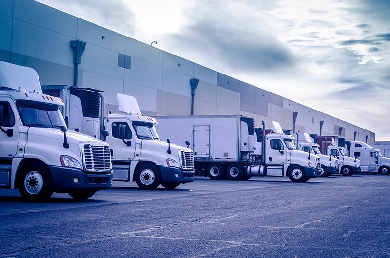 Image of white semi-trucks lined up at warehouse bay doors | TAB Bank